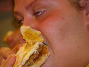 Foto de Byron Solomon mostrando uma pessoa obesa comendo um hambúrguer. Obesidade